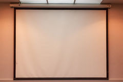 Projection screen in office. Close up white projection screen on beige wall Royalty Free Stock Photography