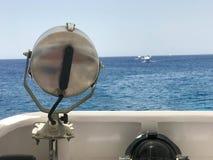Projectoa en kraftig lampa, en ferrimous kraftig lampa för metall M monterade på en carob på bakgrunden av havet, havet, vatten royaltyfri foto