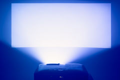 Projector in action with illuminated warm blue screen Stock Photo