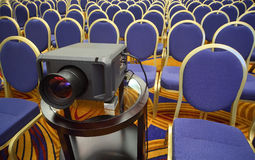 Projector on background of rows of chairs Royalty Free Stock Photos
