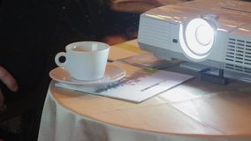 The projector is broadcasting a video. On the projector show a business presentation. On the table is a projector and a