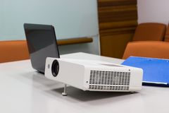 Projector connected to Laptop on for presentation in a meeting room. Projector connected to Laptop on for  presentation in a meeting room, business concept Stock Photos