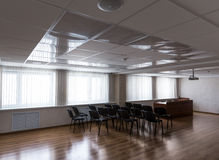 Projector hang on ceiling of empty sunlit meeting room. Empty sunlit modern meeting room with projector hanging on ceiling and black chairs standing in rows Royalty Free Stock Photography
