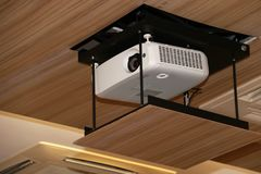 Projector hanging on meeting room ceiling. Projector hanging on the meeting room ceiling stock images