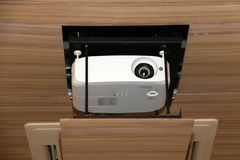 Projector hanging on meeting room ceiling royalty free stock image
