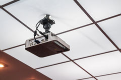Projector installed on the ceiling. Close up modern multimedia projector hanging on ceiling stock photo