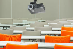 A projector over empty seats with tables in a conference hall. A projector over empty seats with tables in a conference hall stock images