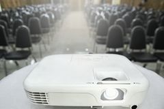 The projector is placed on a table covered with a white cloth pl. Aced in front of the meeting room with placing chairs as regulation for preparing before the Royalty Free Stock Image