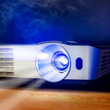 Projector for presentation. Closeup of projector for presentation on wooden table in blue light tone royalty free stock image