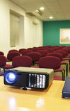 Projector on table with chairs behind (vertical). Projector on table with chairs behind in empty hall (vertical Stock Image