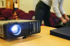 Projector on table with person behind (horizontal) Royalty Free Stock Photo
