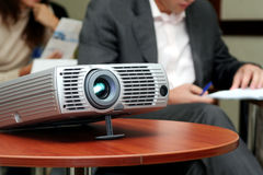 Projector on table with two person behind. (horizontal Stock Image