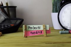 Projects and Funding. Handwriting on sticky notes in clothes pegs on wooden office desk stock photo
