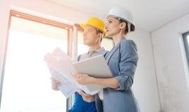 Projektägare och byggnadsarbetare under godtagande arkivfoton