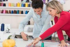 Projektant i aplikant pracuje w dressmaking salonie Zdjęcia Stock