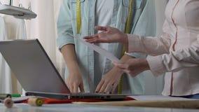 Projektant i pomocnicza przyglądająca sukienna wystawa na laptopie, dyskutuje cienie zbiory