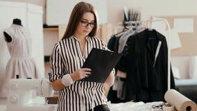 Projektant mody dziewczyna bierze notatki na papierowej pastylce, podnosi, jego spojrzenia przy kamery ono uśmiecha się i oczy zbiory