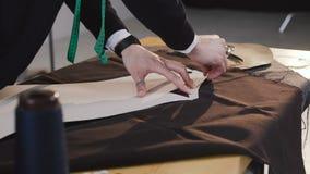 Projektant mody lub krawczyna pracuje z tkaniną przy studiiem pełno krawiectw narzędzia Wzór, nożyce, taśmy miara zdjęcie wideo