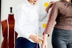 Projektant mody mierzy na części ciała kobiety dla krawczyny ma Obrazy Royalty Free