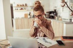 Projektant mody pije kaw? przy jej miejsce pracy zdjęcie stock