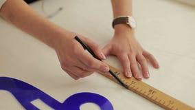 Projektant mody pracuje na stole Ręka kobieta krawczyny rysunku wzór przy papierem w jej studiu kobieta krawczyna z measurin