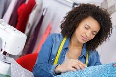Projektant mody tnąca tkanina na dressmaking stole Zdjęcia Royalty Free