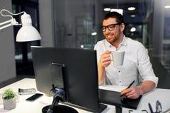 Projektant pije kawę przy biurem z pióro pastylką fotografia stock