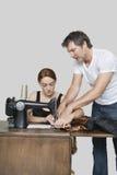 Projektanta pomaga coworker w zaszywania płótnie na szwalnej maszynie nad barwionym tłem Zdjęcia Stock