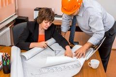 Projektchef och tekniker som diskuterar bygga plan i av arkivbild