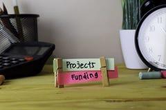 Projekte und Finanzierung Handschrift auf klebrigen Anmerkungen in den Kleiderhaken auf hölzernem Schreibtisch stockfoto