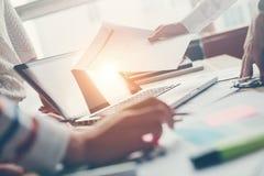 Projektmöte Lag som diskuterar nytt digitalt plan Bärbar dator och skrivbordsarbete på tabellen arkivfoto