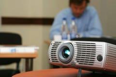 Projektor auf Tabelle mit Person Stockbild