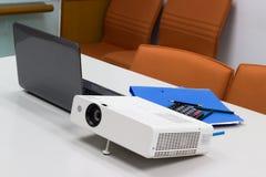 Projektor schloss an Laptop an Dateiordner auf dem Tisch an Stockbilder