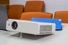 Projektor schloss an Laptop an Dateiordner auf dem Tisch in einem Konferenzzimmer an Lizenzfreie Stockfotos