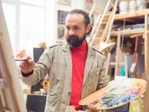Projektujący artysty mężczyzna kończy jego arcydzieło trzyma muśnięcie w ręce Fotografia Royalty Free