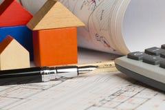 Projet architectural d'une nouvelle maison avec la maison, la calculatrice et les plans mod?les en bois sur la table photo stock