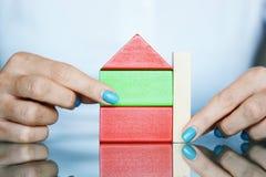 Projet d'immobiliers avec les cubes en bois colorés comme maison chez des mains de la femme Photos libres de droits