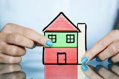 Projet d'immobiliers avec les cubes en bois colorés comme maison chez des mains de la femme Photo libre de droits