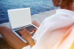 Projet faisant femelle sur le livre net tout en se reposant près de la mer Photo stock