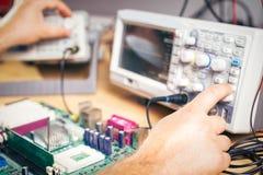 Projete componentes eletrônicos dos testes com o osciloscópio no centro de serviço fotos de stock