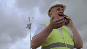 Projete a fala no telefone esperto perto do gerador de vento com painel solar filme