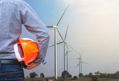Projete o suporte que guarda as turbinas eólicas amarelas da parte dianteira do capacete de segurança que geram a eletricidade Fotografia de Stock