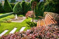 Projeto bonito da paisagem do quintal Vista de árvores coloridas e de rochas aparadas decorativas dos arbustos Fotos de Stock Royalty Free