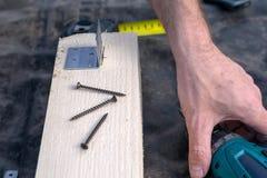Projeto das brocas do homem pela ferramenta Placa de madeira, madeira fotografia de stock royalty free