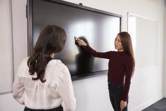 Projeto de And Tutor Discuss do estudante em Whiteboard interativo imagem de stock
