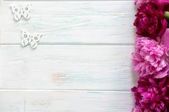 Projeto de uma bandeira floral com peônias e as borboletas brancas Cartão com Borgonha e as peônias cor-de-rosa em um de madeira  fotografia de stock