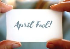 Projeto feliz de April Fools Day mãos que guardaram o cartão Fotografia de Stock