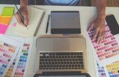 Projeto gráfico e amostras de folha e penas da cor em uma mesa Fotografia de Stock Royalty Free