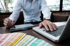 Projeto gráfico e amostras de folha e penas da cor em uma mesa Architectu Foto de Stock