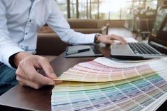 Projeto gráfico e amostras de folha e penas da cor em uma mesa Architectu Fotos de Stock